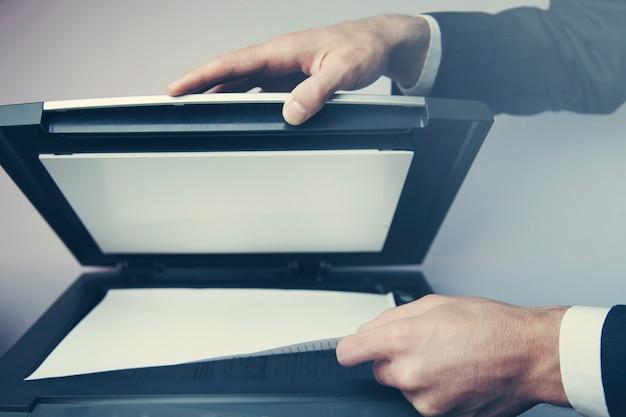 Die hände eines jungen geschäftsmannes legen ein dokument auf einen flachbettscanner