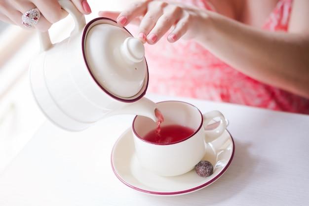 Die hände eines jungen mädchens gossen tee aus einem kessel in eine weiße tasse