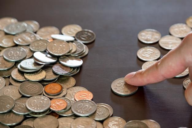 Die hände eines mannes, der gestapelte münzen sortiert.