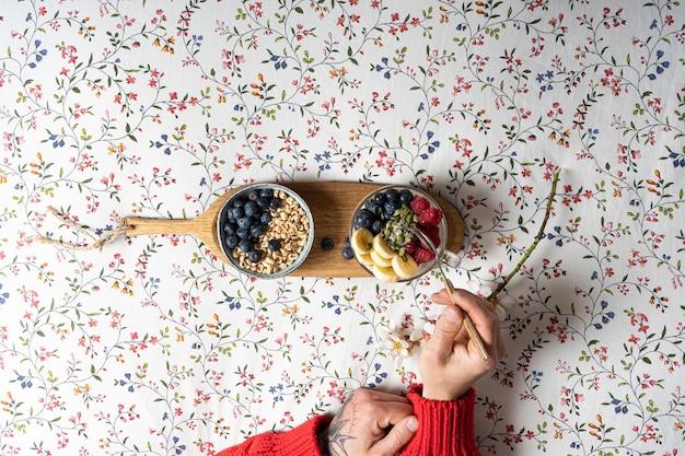 Die hände eines mannes, der im bett eine tasse joghurt mit früchten frühstückt
