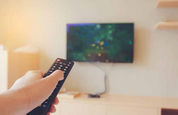 Die hände eines mannes sollten die fernbedienung in der hand drücken, um fernzusehen und sich zu entspannen.