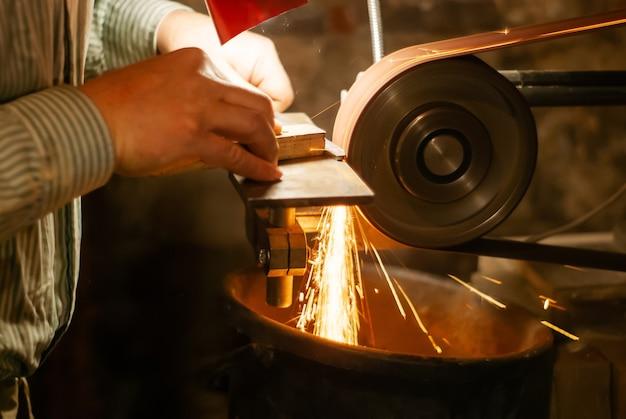Die hände eines schlossers schleifen das werkstück für ein messer auf einem schleifband