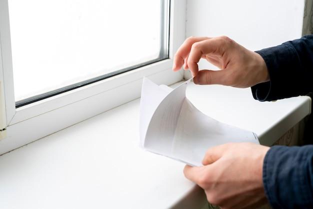 Die hände halten das papier mit dem text und legen es in die konvertierung, um den brief zu senden