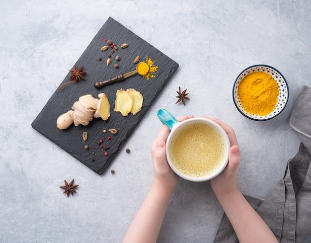 Die hände halten ein glas goldene milch mit kurkuma-gewürzen und honig