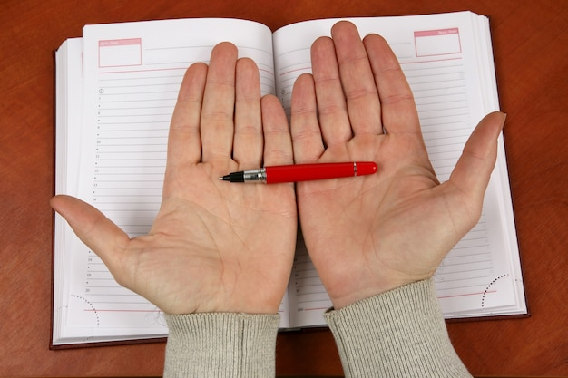 Die hände halten einen roten stift über einem geöffneten notizbuch