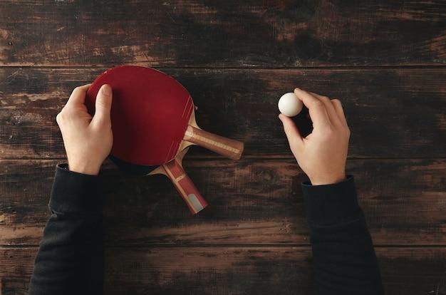 Die hände halten zwei professionelle ping-pong-raketen, angriff plus und verteidigung
