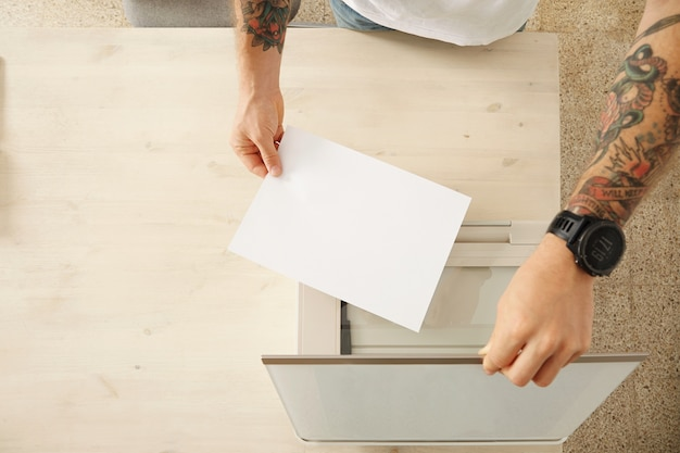 Die hände öffnen ein scannerfach und legen ein blatt papier ein, um ein dokument auf einem multifunktionalen elektronischen heimgerät zu scannen, das auf einem weißen holztisch isoliert ist