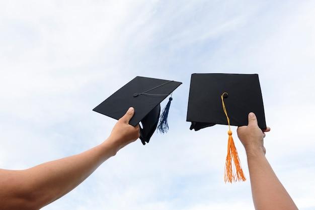Die hände von absolventen, die einen schwarzen hut halten, erstreckten sich in den himmel.