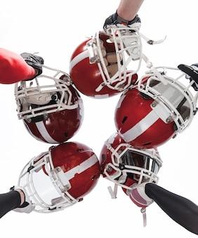 Die hände von american-football-spielern mit helmen auf weißem hintergrund