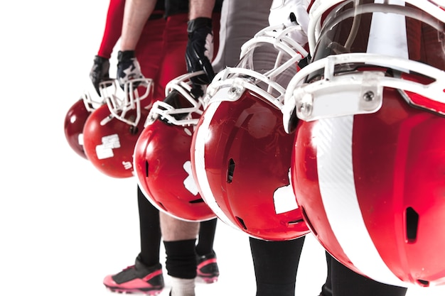Die hände von fünf american-football-spielern mit helmen auf weißem hintergrund
