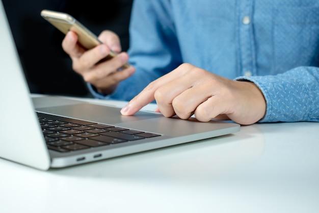 Die hände von leuten benutzen technologie mit computern und telefonen.
