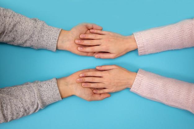 Die hände von mann und frau halten sich gegenseitig auf blau.