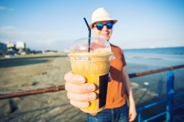 Die hände von mann und frau schließen nah und halten frappe kaffeetasse.