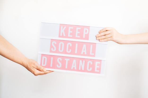 Die hände von mutter und tochter halten ein schild, um soziale distanz zu wahren