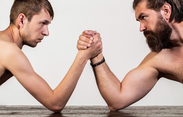 Die hände zweier männer umklammerten das armdrücken, stark und schwach, ungleiches spiel. stark muskulöser bärtiger mann arm ringt einen mickrigen schwachen mann. arme ringen dünne hand, großer starker arm