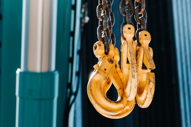 Die haken des mobilkrans in der nähe des glases hoher gebäude. viele haken hängen an ketten, die an einem kran hängen.