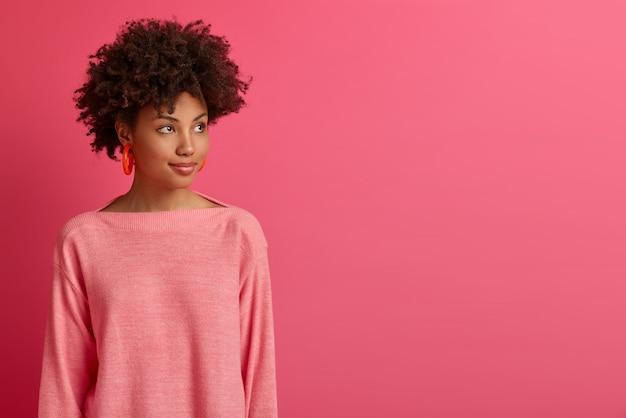 Die halbe einstellung einer nachdenklichen dunkelhäutigen afroamerikanerin wendet sich ab, konzentriert sich irgendwo, überlegt sich bessere wege, hat etwas im sinn, trägt einen langärmeligen pullover, isoliert auf einer rosa wand