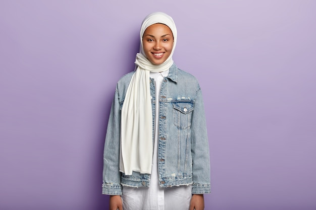 Die halbe länge der fröhlichen araberin trägt einen weißen hijab und eine jeansjacke