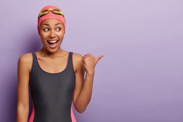 Die halbe länge des glücklichen schwimmers trägt eine schwimmbrille und einen badeanzug