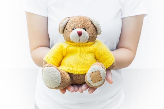 Die haltene und schützende frau geben gelbe hemden einer braunen teddy bear-spielzeugabnutzung, die auf weißer hintergrundnahaufnahme, symbol der liebe oder datierung sitzen