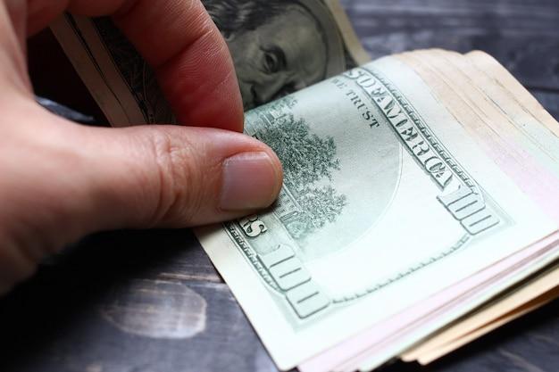 Die hand berechnet den dollar in nahaufnahme