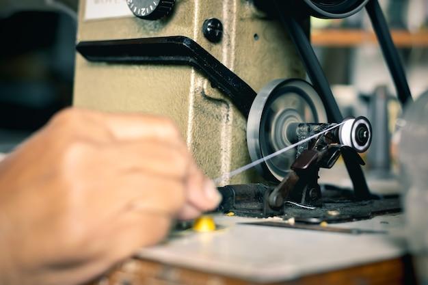 Die hand der alten frau näht faden zur nähmaschine.