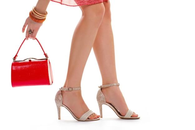 Die hand der dame hält roten geldbeutel. beige absätze und armbänder. beine des jungen modells. designerschuhe und kleine accessoires.