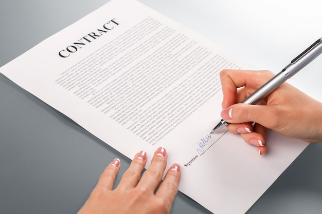 Die hand der dame unterschreibt einen werbevertrag. weibliche hand unterzeichnet fördervertrag. wir werden ihnen helfen. unternehmen sollten sich gegenseitig helfen.