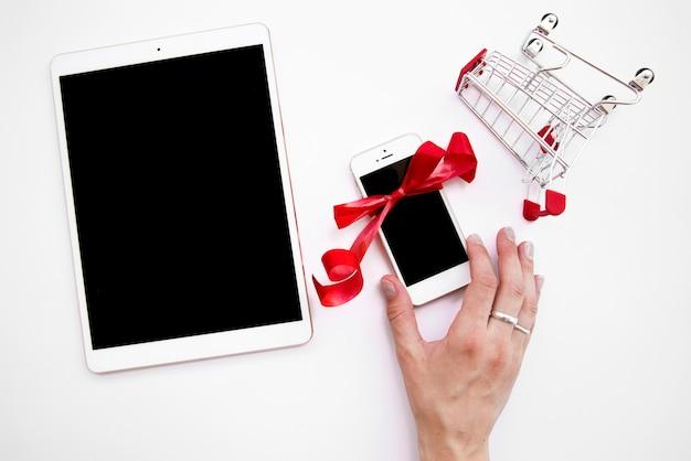 Die hand der frau auf smartphone nahe tablette und einkaufslaufkatze