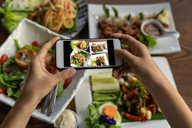 Die hand der frau benutzt ein handy, um ein foto von essen auf dem esstisch im restaurant zu machen.