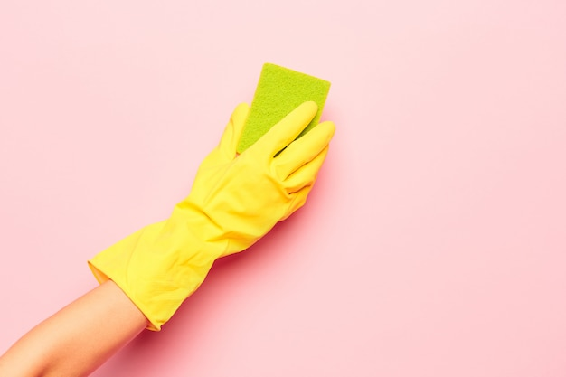 Die hand der frau, die an einer rosa wand putzt. reinigungs- oder reinigungskonzept