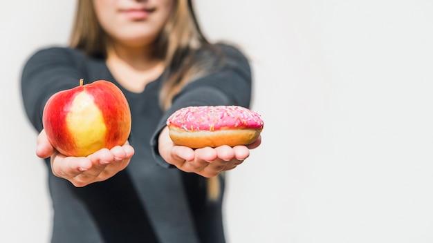 Die hand der frau, die apfel und donut hält