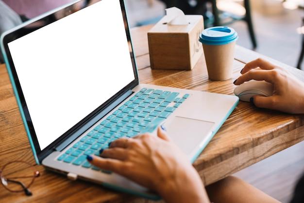 Die hand der frau, die auf dem laptop im café schreibt