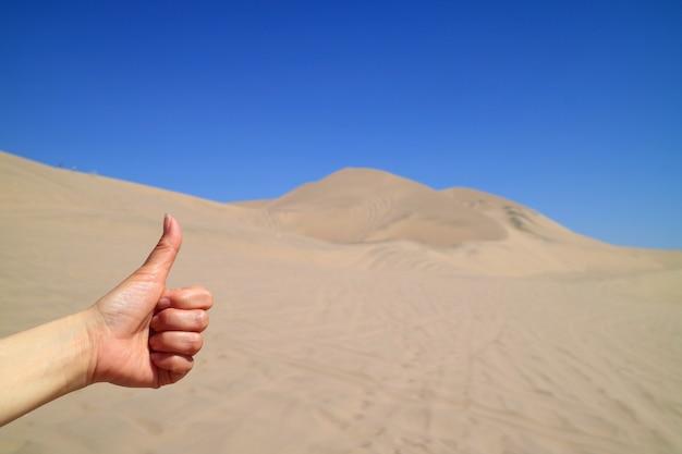 Die hand der frau, die bis zur erstaunlichen ansicht von huacachina-wüste in ica-region von peru abgreift
