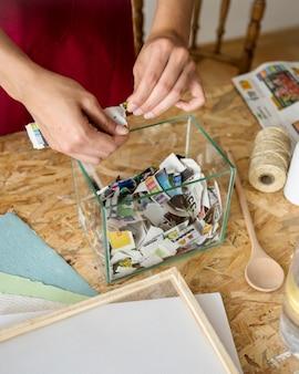 Die hand der frau, die blätter papier in behälter einsetzt
