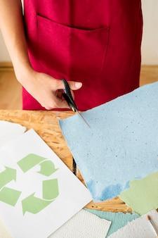 Die hand der frau, die blaues papier mit scheren schneidet