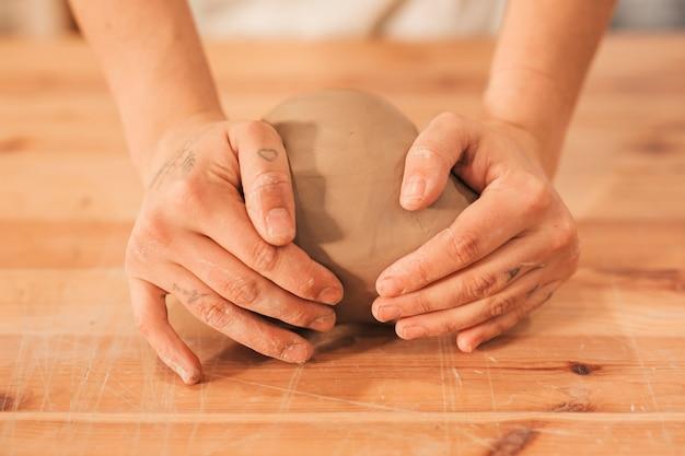 Die hand der frau, die den lehm auf holztisch knetet
