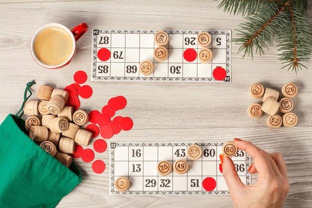 Die hand der frau, die ein fass für ein spiel im lotto hält. hölzerne lottofässer mit grüner tasche, spielkarten, roten chips und tasse kaffee, weihnachtstannenzweigen. brettspiel lotto. ansicht von oben