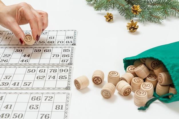 Die hand der frau, die ein fass für ein spiel im lotto hält. lottofässer aus holz mit grüner tasche und spielkarten. weihnachtstannenzweige im hintergrund. brettspiel lotto
