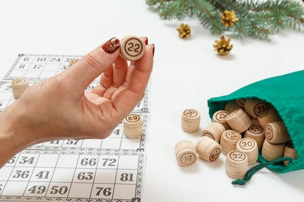 Die hand der frau, die ein fass mit einer zahl zweiundzwanzig für ein spiel im lotto hält. lottofässer aus holz mit grüner tasche und spielkarten. weihnachtstannenzweige im hintergrund. brettspiel lotto