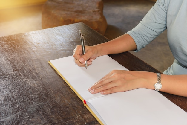 Die hand der frau, die ein gästebuch mit einem stift unterzeichnet