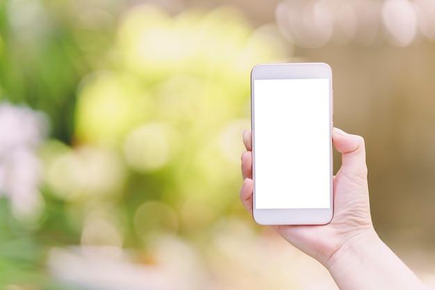 Die hand der frau, die ein smartphone mit weißem leerem bildschirm für sms hält - auf unscharfem hintergrund.