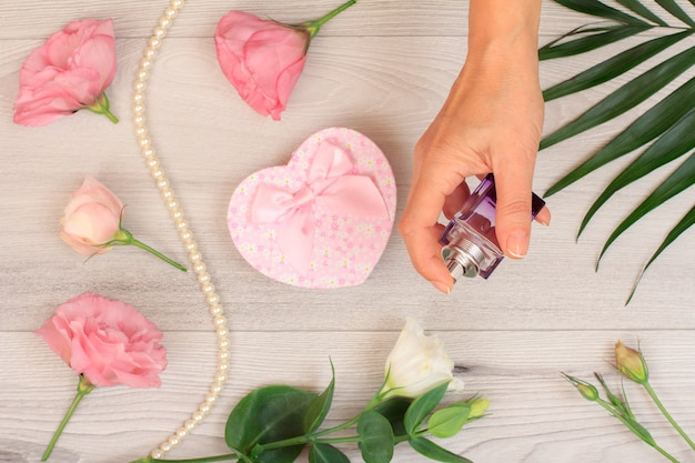 Die hand der frau, die eine flasche parfüm über grauem hölzernem hintergrund mit herzförmigem kasten, schönen blumen und grünen blättern hält. konzept, an feiertagen ein geschenk zu machen. ansicht von oben.
