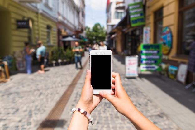 Die hand der frau, die foto auf mobiltelefon an der straße macht