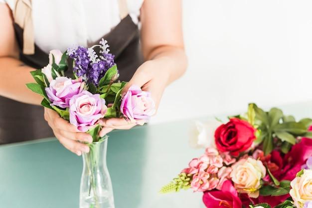 Die hand der frau, die frische blumen im vase vereinbart