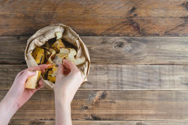 Die hand der frau, die fruchtschalen in der papiertüte auf hölzernem hintergrund ablegt. recycling-konzept.