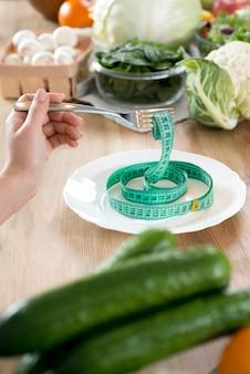 Die hand der frau, die gabel mit grünem maßband auf weißer platte über küchenarbeitsplatte hält