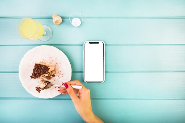 Die hand der frau, die gebäck mit getränk und mobiltelefon auf tabelle isst