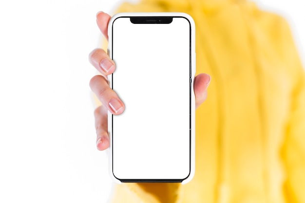 Die hand der frau, die handy mit leerem weißem schirm zeigt