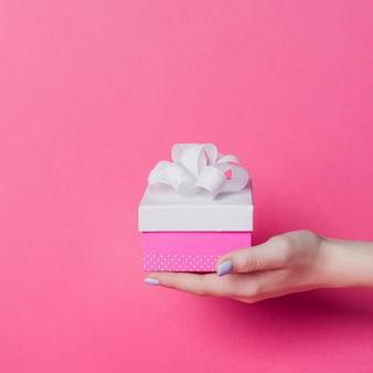 Die hand der frau, die kasten mit weißem band hält, beugen auf rosa hintergrund